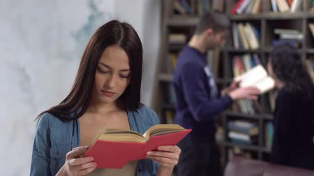Young brunette woman at library reading book surprised