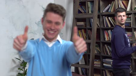 interessado : Young man in library showing thumbs up blurred guy at back looking at him curious