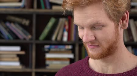 Red-haired man in library reading story joyful Стоковые видеозаписи