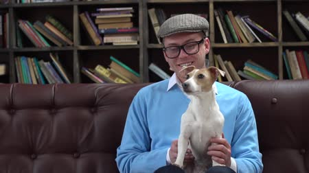 Young man in library in eyeglasses and flat cap sitting holding dog joyful