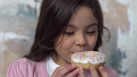Little girl alone isolated on painted wall biting donut glaze delightful Стоковые видеозаписи