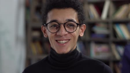 Young man in library in eyeglasses smiling joyful Стоковые видеозаписи