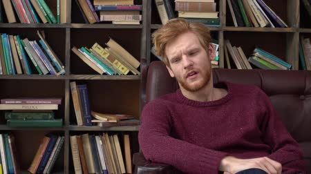 Red-haired man sitting in library taking off glasses