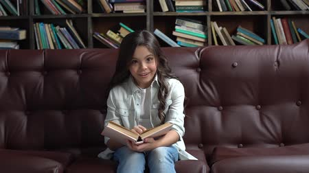 Little girl sitting in library reading book looking camera curious Стоковые видеозаписи