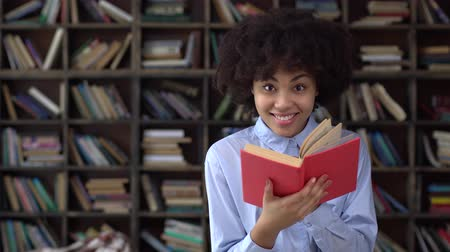 Young african woman in library reading book looking camera cheerful Stock mozgókép
