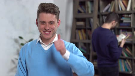 kciuk : Young man in library looking camera joyful showing thumb up Wideo