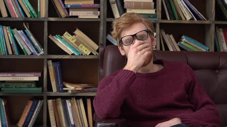 Red-haired man sitting in library massaging nasal bridge