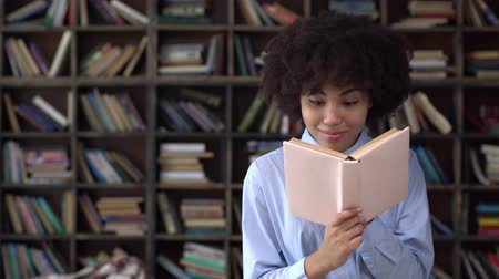 Young african woman in library closing book smiling happy Stock mozgókép