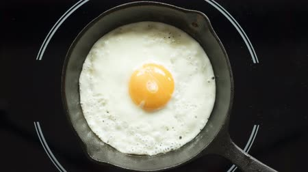 Fried egg on a pig-iron frying pan preparation process time lapse. 影像素材