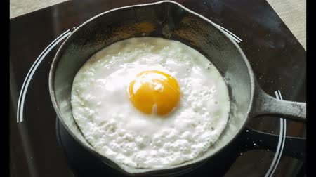 prase : Fried egg on a pig-iron frying pan preparation process time lapse. Dostupné videozáznamy