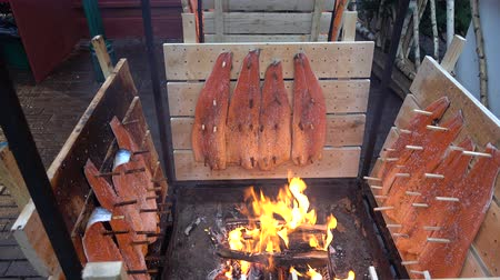 Salmon is smoked on open fire at Christmas market in Hannover. Germany.