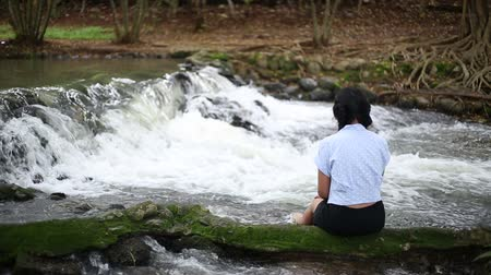 A woman sitting by the Nam Tum waterfall in Chanthaburi at thailand