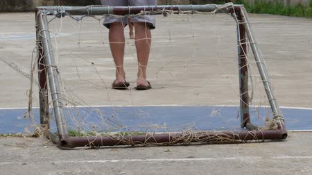 Pool boy kicking old football have laceration and net laceration small goal with man.