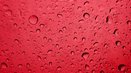 совершенство : Rain water Drops On red Background.