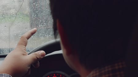 knock : Man hands on steering wheel of car focus in. Fingers knock on the hard rain.