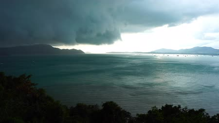 гром : Storm clouds and rain over sea Dark storm clouds passing mountain