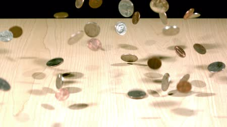 slow motion coins bouncing on table