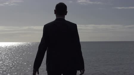 businessman silhouette standing on a sunny beach in the morning slow motion