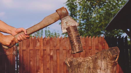 насилие : young strong man is chopping wood outdoors slow motion