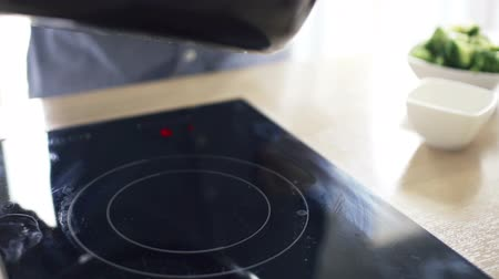 super bowl : man spreading olive oil on pan over induction hob in kitchen slow motion