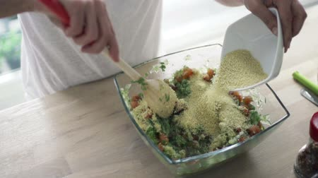 bowls : woman mixing salad with wooden spoon and adding couscous slow motion Stock Footage