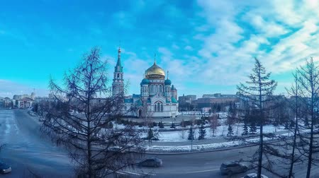 City landscape, in the center of which is an Orthodox church, the movement of cars and people. Clouds in the blue sky. Time-lapse