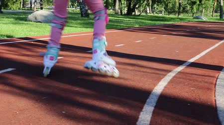 A girl in pink clothes skates in a roller-skating park in the evening Stock Footage
