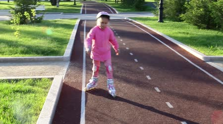 A seven-year-old girl learns rollerblading in a summer park on a bicycle path