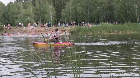 People rest on a pond in a city park and ride a catamaran