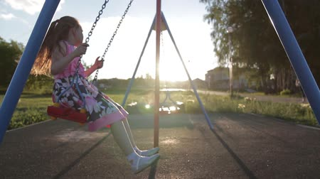 Seven year old cheerful girl in a pink dress swinging on a swing in the park at sunset Stock Footage