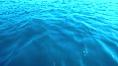 Rapid movement of the camera forward along the water texture of the sea with a blue tint without waves and splashes from the body of the boat. In the water reflect the rays of the sun at sunset Stock Footage