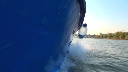The hull of the blue boat on the left side, the movement along the river in good weather without large waves Stock Footage