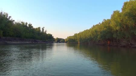 traffic on the narrow boat on the Siberian river along a desert coast in the summer Stock Footage