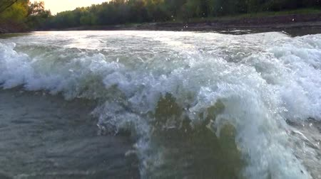 Wake from the propeller of a boat moving on a dull desert the river along steep banks Stock Footage