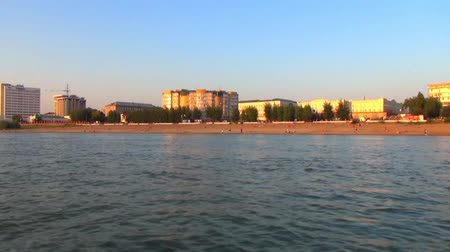 The building of the city river station of the Siberian city, Russia, shooting at the side of the boat at sunset Stock Footage