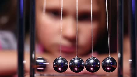 A little girl has problems in school, in frustrated feelings sits at the table and launches balls of the cradle of Newton
