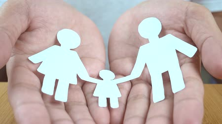 promover : close up of man cupped hands showing paper man family Stock Footage