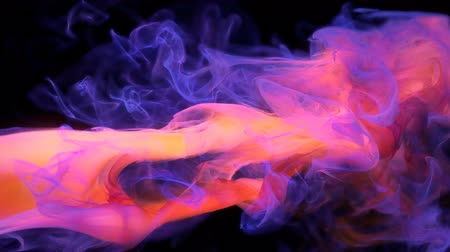 Orange purple color paint ink drops in water slow motion art background with copy space. Inky cloud swirling flowing underwater. Abstract smoke fluid  liquid animation isolated on black alpha channel
