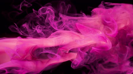 Pink color paint ink drops in water. Slow motion art background with copy space. Inky cloud swirling flowing underwater. Abstract smoke fluid liquid animation isolated on black alpha channel 4k