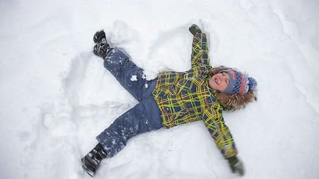 snow angel : Adorable little boy in green jacket, lying on north pole snow, making snow angely making snow angel