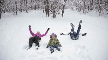 snow angel : Family making snow angel, laying down on snow Stock Footage