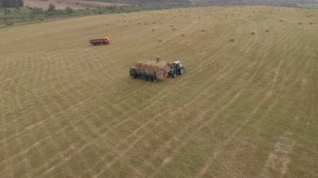 Aerial view drone of harvest field with tractor moving hay bale Vídeos