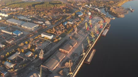 zvyk : TOMSK, RUSSIA - August 25, 2018: Port river cranes loading ships on barges delivery, sunset. Aerial drone