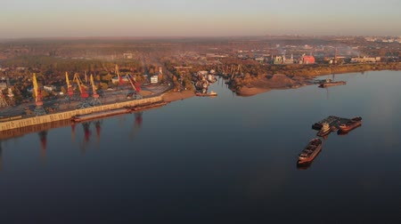 Port river cranes loading ships on barges delivery, sunset. Aerial drone Vídeos