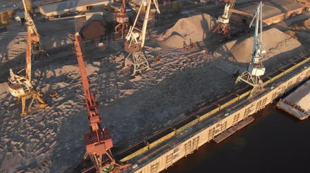 unload : TOMSK, RUSSIA - August 25, 2018: Port river cranes loading ships on barges delivery, sunset. Aerial drone