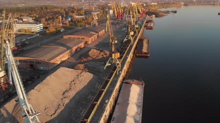 TOMSK, RUSSIA - August 25, 2018: Port river cranes loading ships on barges delivery, sunset. Aerial drone