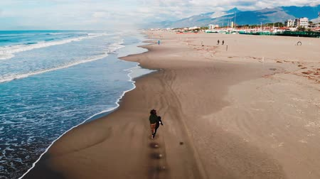Aerail drone, Girl tourist runs along beach viareggio italy wave line in jeans. Freedom concept.