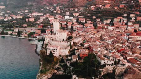 Lake Lago Garda - view of Malcesine village. Old castle on rock Italy. Aerial video sunset.