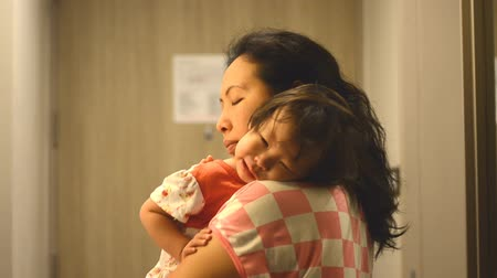 капелька : Little Asian girl crying on mother shoulder at night time