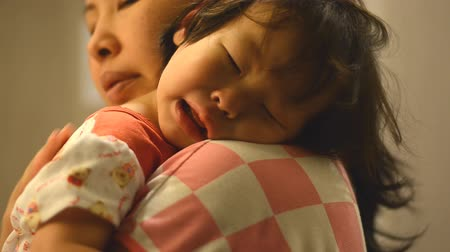 little : Little Asian girl crying on mother shoulder at night time